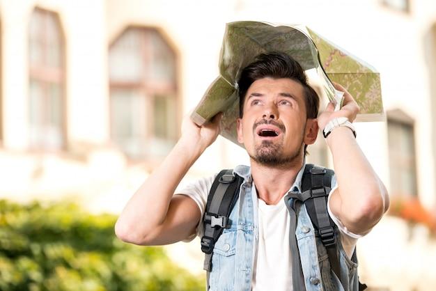 Glücklicher junger mann, tourist in der stadt mit touristischer karte.