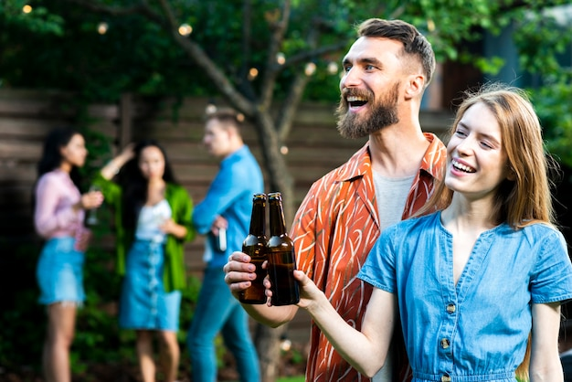 Glücklicher junger mann und frau, die bier röstet