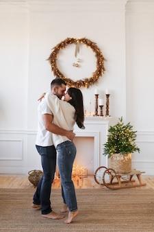 Glücklicher junger mann und frau, die spaß haben, am dekorierten kamin zu küssen und zu tanzen
