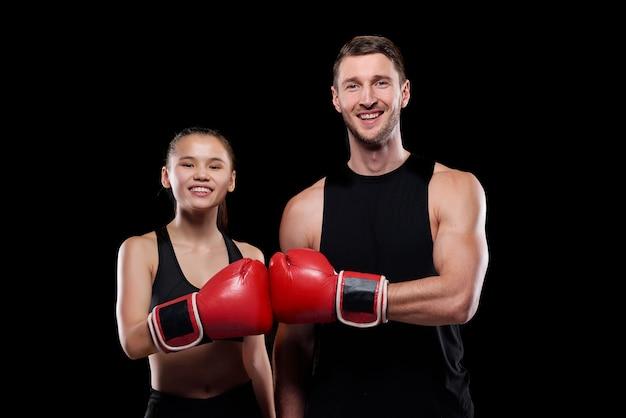 Glücklicher junger mann und frau in der aktivkleidung, die sie mit einem lächeln betrachten, während sie einander hände in den boxhandschuhen berühren