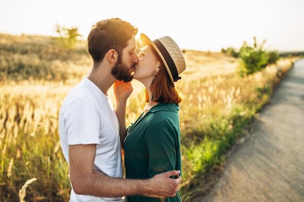Glücklicher junger mann und frau lächelnd und umarmt draußen bei sonnenuntergang. konzept von menschen, liebe und lebensstil