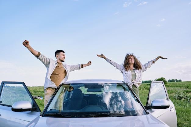 Glücklicher junger mann und frau mit ausgestreckten armen, die durch offene türen ihres autos stehen und warmen sommertag gegen blauen himmel genießen