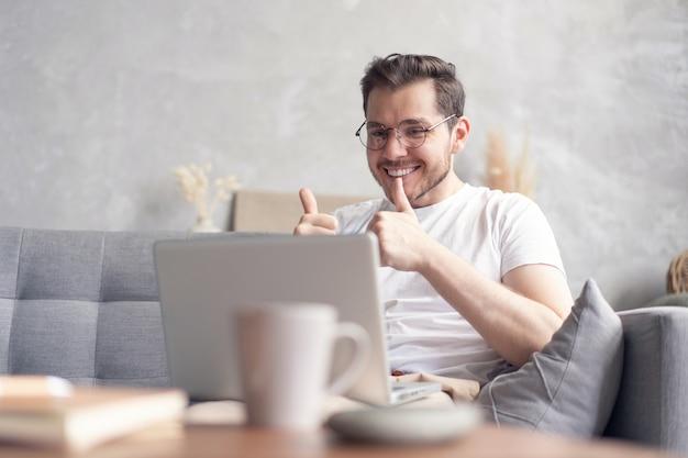 Glücklicher junger mann video-chat auf laptop-computer beim sitzen auf dem sofa zu hause