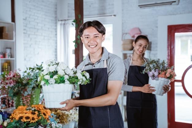 Glücklicher junger mannflorist, der schürze hält, die eimerblume lächelt und kamera betrachtet. arbeit im blumenladen mit seinem freund dahinter