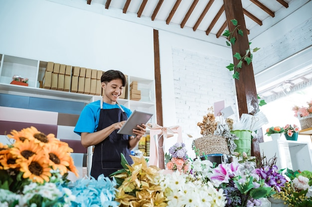 Glücklicher junger mannunternehmer, der im blumenladen arbeitet, der schürze lächelt, während tablette hält