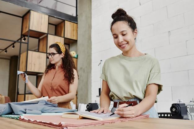 Glücklicher junger modedesigner, der auf skizze für neue saisonale sammlung von kleidern zeigt oder sie zeichnet, während er am tisch steht