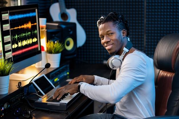 Glücklicher junger musiker mit kopfhörern am hals, der sie beim arbeiten über neue musik am arbeitsplatz im studio ansieht