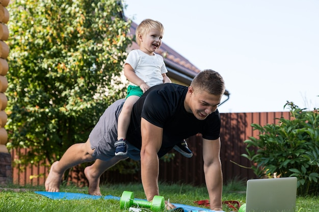 Glücklicher junger papa spielt mit ihrem baby auf einem grünen rasen. konzept einer glücklichen familie. vatertag. papa und sohn haben gemeinsame aktivitäten im urlaub im hinterhof