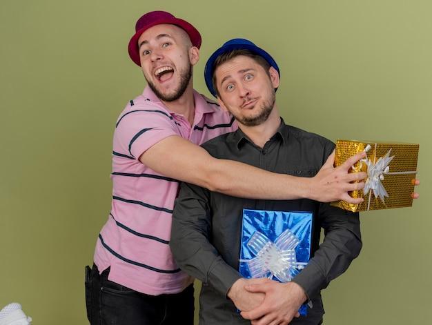 Glücklicher junger party-typ, der roten hut trägt, hält geschenkbox und umarmungen beeindruckte kerl, der geschenkbox hält, der blauen hut trägt, der auf olivgrün isoliert wird