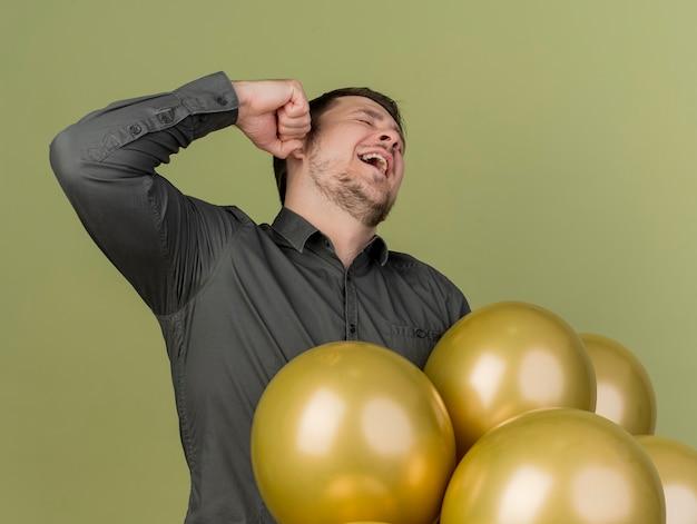 Glücklicher junger party-typ, der schwarzes hemd trägt, das neben ballons steht, die ja geste lokalisiert auf olivgrün zeigen