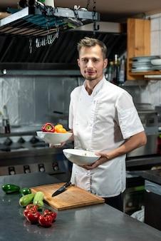 Glücklicher junger profikoch, der am tisch steht und zwei keramikschalen mit frischer paprika für gemüsesalat oder andere gänge hält