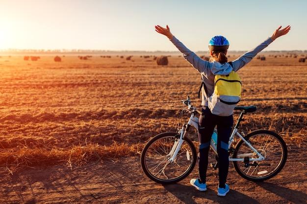 Glücklicher junger radfahrer, der im herbstfeld geöffnete arme anhebt und die aussicht bewundert. frau fühlt sich frei. den sieg feiern