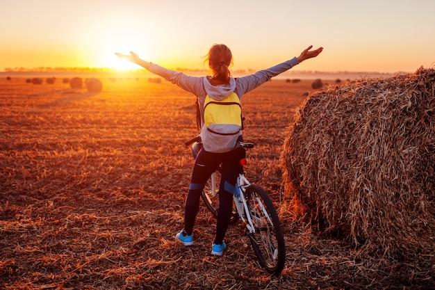 Glücklicher junger radfahrer, der im herbstfeld geöffnete arme anhebt und die aussicht bewundert. frau reiches ziel. freie energie