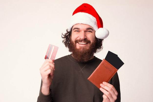 Glücklicher junger reisender trägt eine weihnachtsmütze, während er pass- und flugtickets hält.