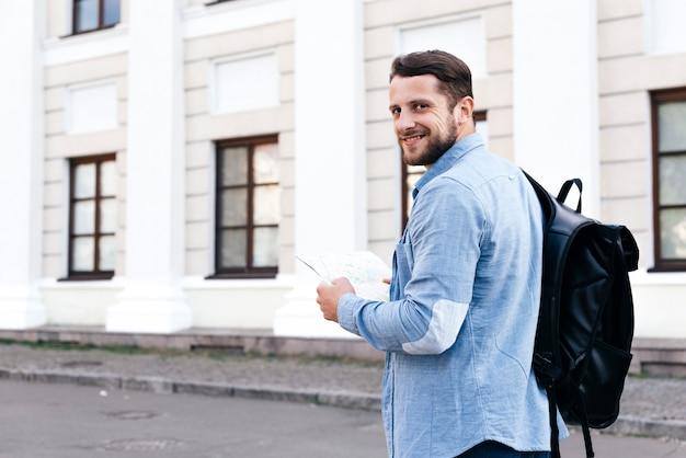 Glücklicher junger reisendmann, der karte hält und kamera betrachtet