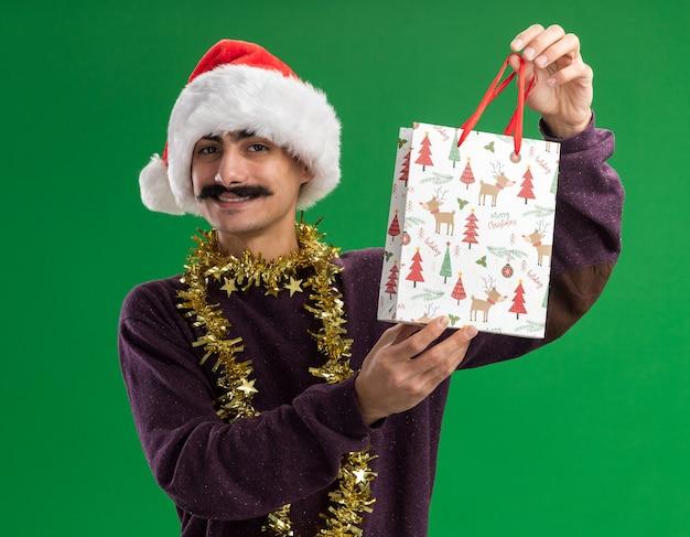 Glücklicher junger schnurrbartmann, der weihnachtsweihnachtsmütze mit lametta um seinen hals trägt, der papiertüte mit weihnachtsgeschenk hält, die kamera betrachtet, die zuversichtlich über grünem hintergrund steht