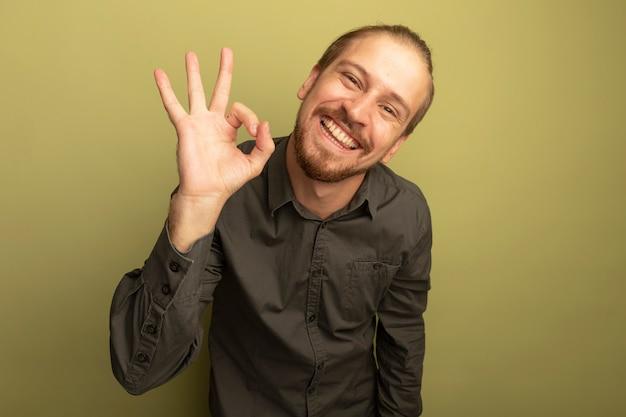 Glücklicher junger schöner mann im grauen hemd, das ok zeichen lächelnd zeigt