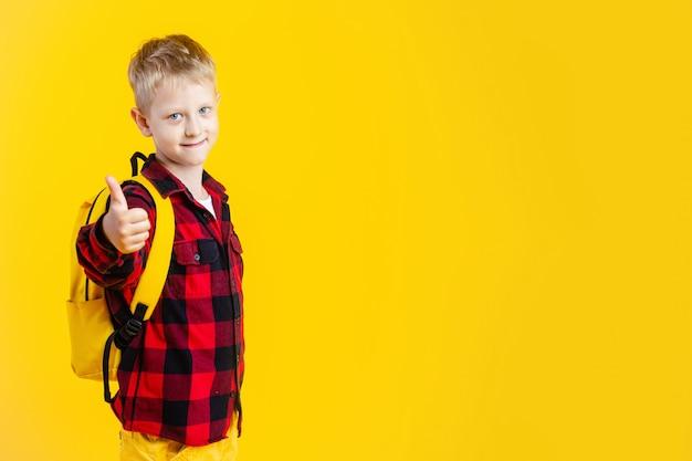 Glücklicher junger schuljunge hält rucksack mit daumen hoch auf gelbem hintergrund.
