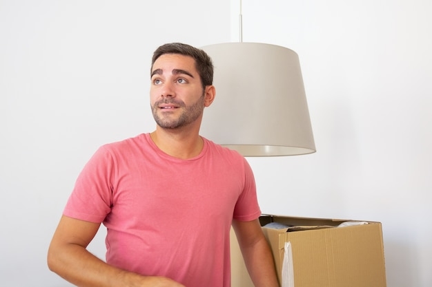 Glücklicher junger spanischer mann, der sachen in seiner neuen wohnung auspackt, in der nähe von kartons steht und wegschaut