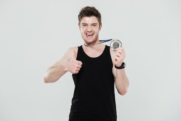Glücklicher junger sportler, der medaille hält