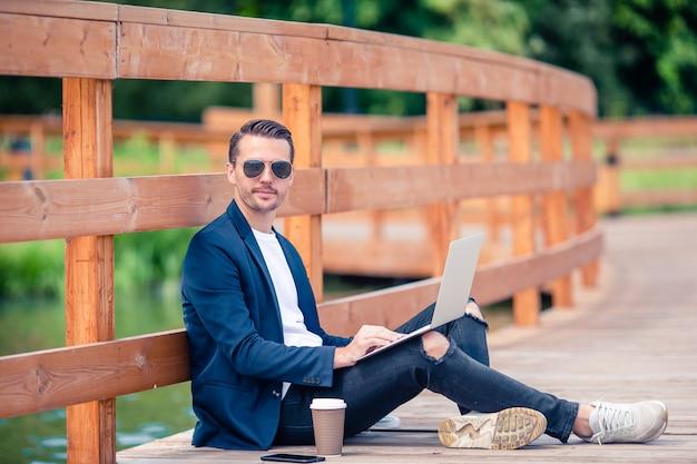 Glücklicher junger städtischer mann, der draußen kaffee in der europäischen stadt bearbeitet und trinkt