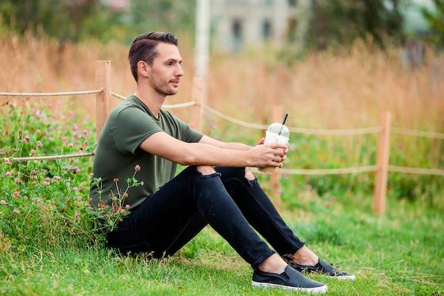 Glücklicher junger städtischer mann mit buch draußen