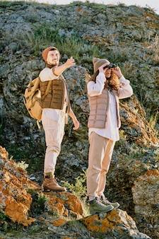 Glücklicher junger tourist mit rucksack, der nach vorne zeigt, während er auf felsen hinter seiner frau steht und durch fernglas während der reise schaut