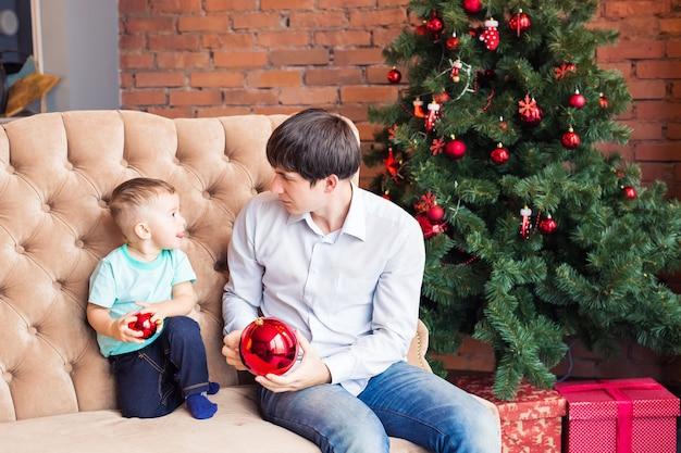 Glücklicher junger vater, der mit seinem kleinen sohn nahe weihnachtsbaum spielt