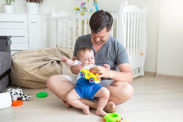 Glücklicher junger vater, der mit seinem kleinkindsohn auf dem boden spielt