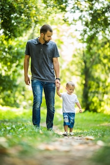Glücklicher junger vater, der seinen kleinen sohn an der hand hält und auf dem park geht