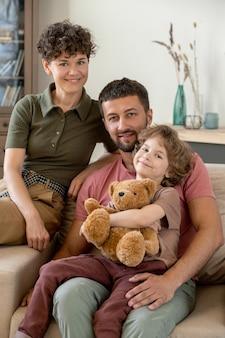 Glücklicher junger vater, der seinen niedlichen kleinen sohn mit teddybär auf den knien hält, während hübsche frau nahe auf ihnen auf bequemer couch sitzt