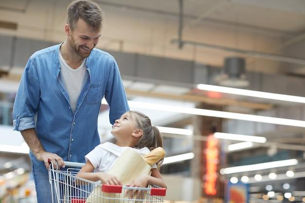 Glücklicher junger vater im supermarkt