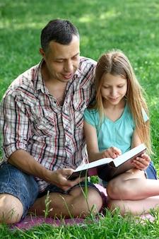 Glücklicher junger vater mit einer tochter, die die bibel liest