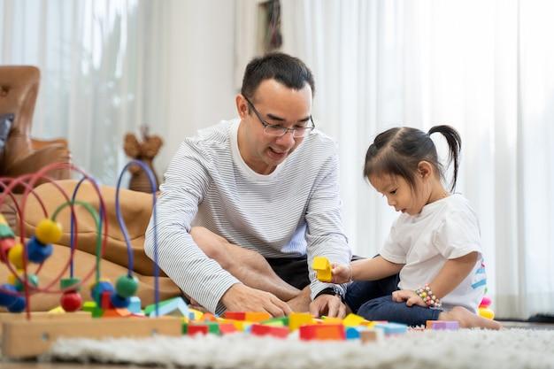 Glücklicher junger vater und mutter und eine kleine tochter, die mit spielzeug-holzblöcken spielt, auf dem boden im wohnzimmer, familie, elternschaft und menschenkonzept mit entwicklungsspielzeug sitzt