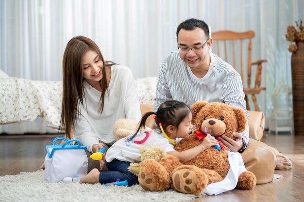 Glücklicher junger vater und mutter und eine kleine tochter, die mit spielzeug spielen und auf dem boden im wohnzimmer-, familien-, elternschafts- und personenkonzept sitzen