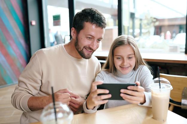 Glücklicher junger vater und seine tochter, die lustiges video im smartphone ansehen, während sie zeit im café verbringen