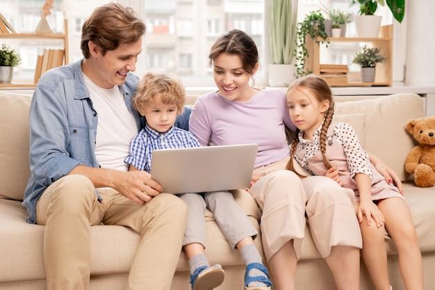 Glücklicher junger verheirateter mann und frau und zwei niedliche kinder, die laptopanzeige beim ansehen des films zu hause betrachten