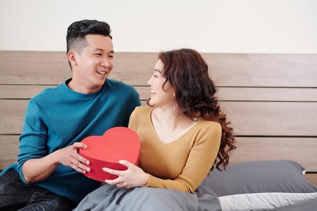 Glücklicher junger vietnamesischer mann, der seiner lächelnden hübschen freundin ein valentinstagsgeschenk gibt