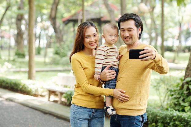 Glücklicher junger vietnamesischer mann, der selfie mit frau und kleinem sohn spricht, wenn sie im park gehen