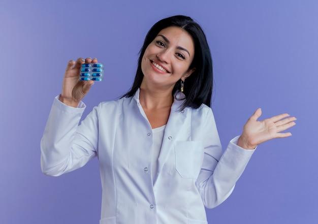 Glücklicher junger weiblicher arzt, der medizinische robe trägt packung der medizinischen kapseln, die leere hand suchen und zeigen