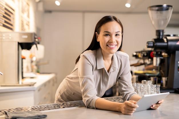 Glücklicher junger weiblicher barista mit digitalem tablett, der sie beim stehen am arbeitsplatz betrachtet und neues menü für die woche hochlädt