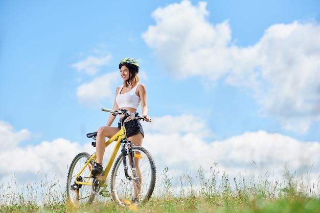 Glücklicher junger weiblicher fahrer, der auf gelbem fahrrad auf einem gras fährt