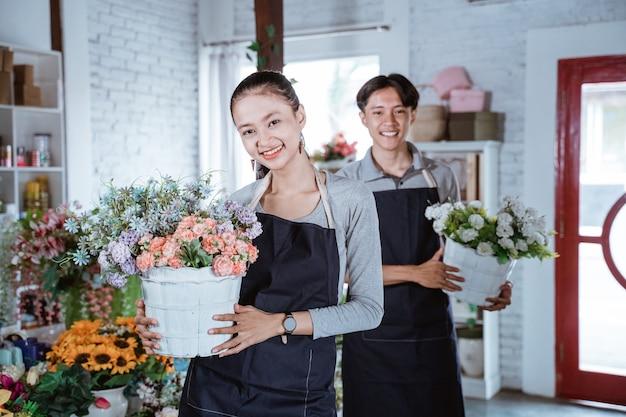 Glücklicher junger weiblicher florist, der schürze hält, die eimerblume lächelt, kamera betrachtend. arbeit im blumenladen mit ihrer freundin dahinter