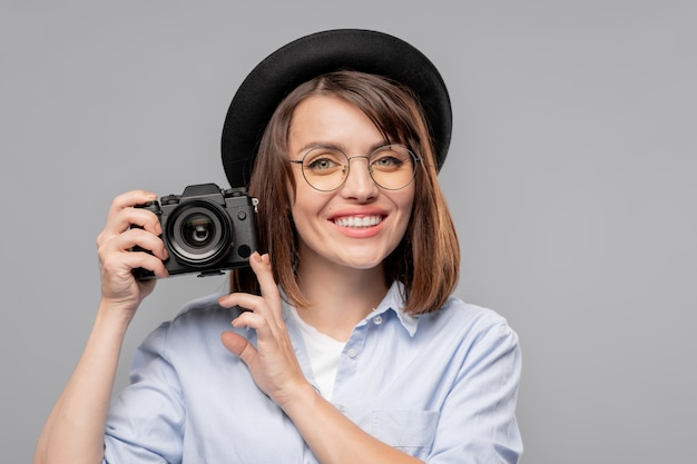 Glücklicher junger weiblicher fotograf mit zahnigem lächeln, das sie aufpasst