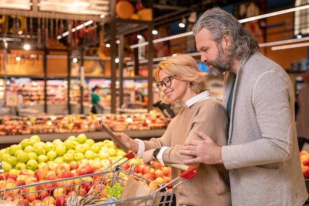 Glücklicher junger weiblicher käufer, der ihren ehemann einkaufsliste im notizblock zeigt, während beide entlang anzeige mit frischen äpfeln gehen