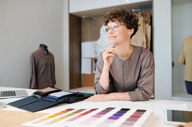 Glücklicher junger weiblicher kreativer designer, der an ideen denkt, während er über neue sammlung durch arbeitsplatz arbeitet