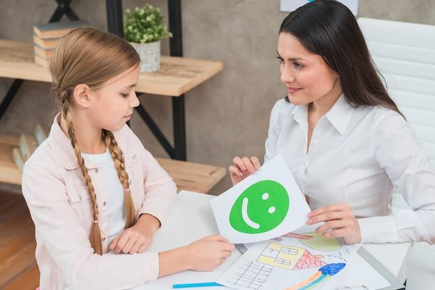 Glücklicher junger weiblicher psychologe, der dem blonden mädchen glückliche grüne gefühlgesichtskarte zeigt