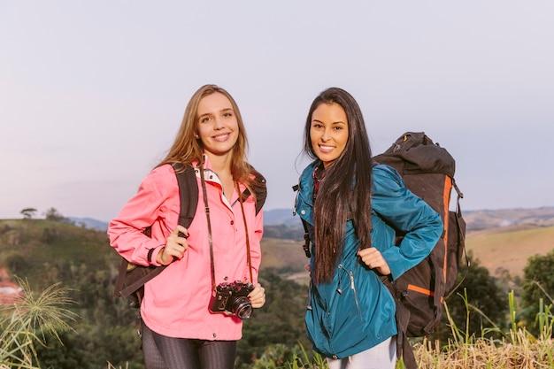 Glücklicher junger weiblicher reisender zwei mit rucksack und kamera