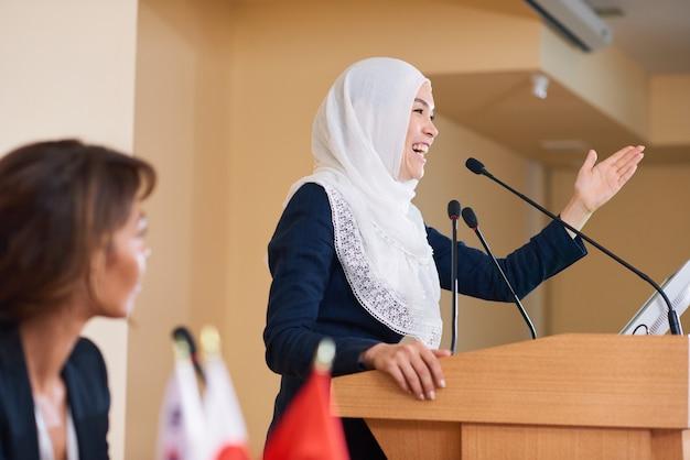 Glücklicher junger weiblicher sprecher im hijab, der lacht, während er auf der konferenz durch tribüne steht und mit publikum spricht