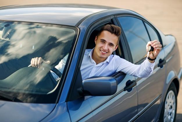 Glücklicher käufer, der autoschlüssel in seinem neuen fahrzeug hält